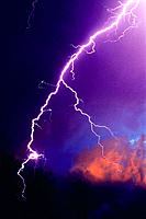 A lightning bolt pierces the storm clouds at dusk, typical of stormy weather in the tropics