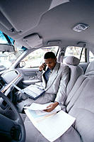 Executive in car with cell phone and laptop computer