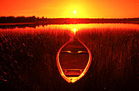 Boat at rest on lake at sunrise