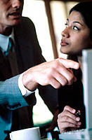 Latino business woman listens to business man making a point