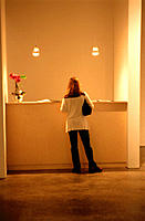 Full length back view of a woman standing at a reception desk