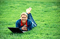 Young woman lays in grass with laptop and cell phone