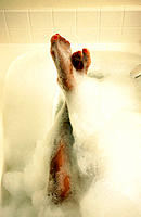 African-American woman´s legs and feet in bubble bath