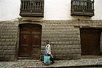 Woman walking past colonial building built upon ancient Inca foundation. Cuzco. Peru