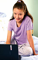 Young girl working on laptop in her bedroom