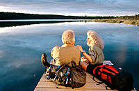 Senior couple of hikers on dock at sunset. Otter Lake. Alaska. USA