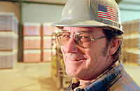 Portrait of mid-50's man in hard hat, wharehouse in background