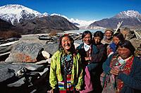 Women and Mani stones in front of Lhagu peaks. Tibet