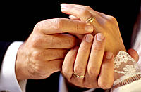 Man putting wedding ring on woman's hand close up