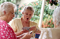Three mature women playing cards