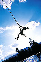 Boy Swinging on Rope Over Lake, Silhouette