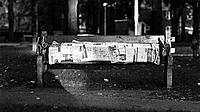Two homeless covered by newspapers share a bench