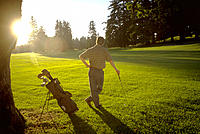 Golfer from behind with sun reflecting behind trees