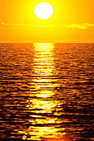 Golden sunset over ocean water, reflection on shimmering water