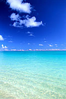 Calm shallow water fades to turquoise, horizon lined w/ small clouds