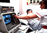 Heart ultrasound scan. Nurse using an echocardiograph machine to study a patient´s heart. This technique uses ultrasound to detect the heart´s structu...
