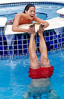 Woman holds man's feet as he stands on hands in pool