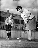Two mature women playing golf