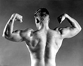 Rear view of a male body builder flexing his muscles