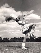 Drum majorette performing with a twirling baton in a field