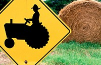 Farm tractor sign and round hay bale