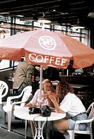 Two Women Sitting at an Umbrella Table, Coffee Shop