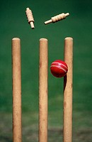 A cricket ball hits the stumps and the bails fly off
