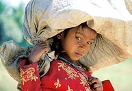 Girl carrying a sack on her head. Kerala. India