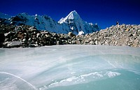 Climber under Wedge Peak. Ice covered pond above Pangpema. Kangchenjunga. East Nepal