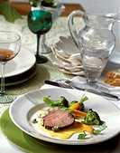 Beef fillet in herb crust on saffron sauce with vegetables