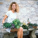 Young woman sitting on a bench with fresh herbs