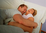 Couple Hugging and Laughing in Bed