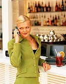 Businesswoman using Cell Phone at Bar with Laptop