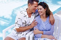 Middle aged couple in patio chairs near pool