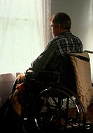 Disability and depression. A disabled man confined to a wheelchair gazes out of his window. Depression is a common consequence of disability, especial...