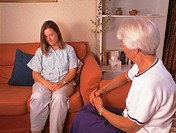 Counselling. Anguished woman receiving counselling from a female counsellor (right). Counselling is advice and psychological support given by a health...