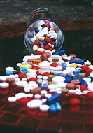 CREDIT: TRACY DOMINEY/SCIENCE PHOTO LIBRARY Assorted pills spilling from a glass.