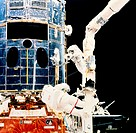 Servicing the Hubble Space Telescope. Astronauts Jeffrey Hoffman (foreground) and Story Musgrave seen servicing the Hubble Space Telescope during Shut...