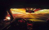 View from inside car, with blurred lights and traffic in the distance