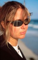 Young woman looking into the distance. Sunglasses reflect departing man