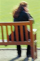 Woman sitting on a park bench, talking on cellular phone