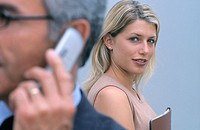 Businessman with cell phone in front, businesswoman in the background looking at camera