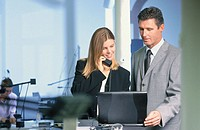 Two businesspeople in front of laptop, businesswoman talking on phone