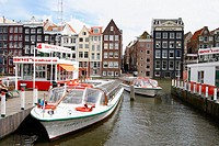 Cruise boats at Damrak. Amsterdam. Holland