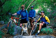 Group of mountain bikers and a dog take a break