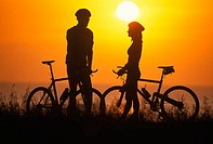 Silhouette of a man and woman mountain biking near the coast at sunset
