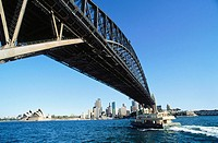 Ferry passing under Harbour Bridge. Sydney. Australia