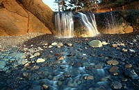 Fall creek tumbles over a waterfall onto the beach at sunset. Hug Point State Recreation Site. Oregon. USA