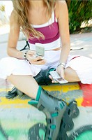 Teen girl with cell phones and rollerblades