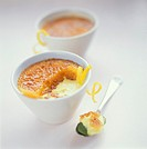 Crème brulee with lemon zest in a bowl and on a spoon
